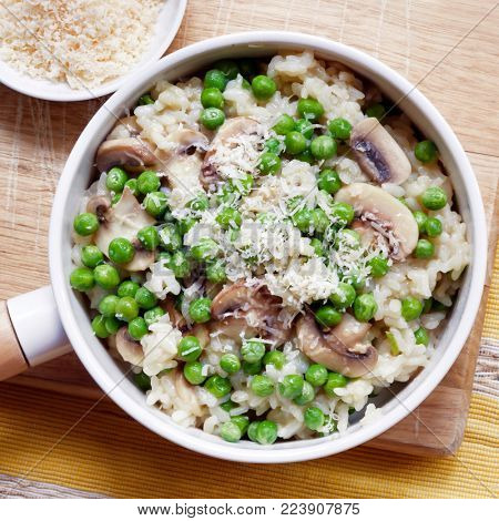 Risotto with mushrooms, peas and parmesan cheese, top view.