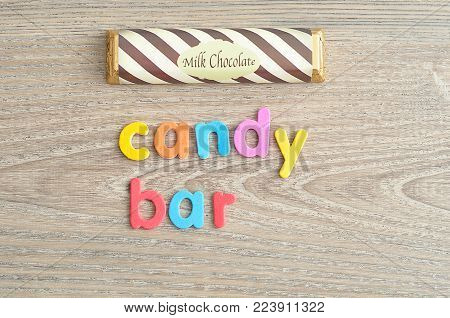 A candy bar with a wrapper isolated on a wooden background with the word candy bar poster