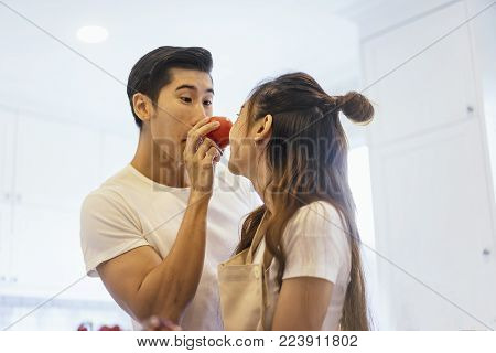 Beautiful asian young couple is looking to cooking in kitchen at home,Happy young woman washing vegetables in the sink and handsome man playing with her.