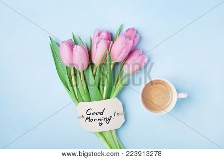 Coffee cup, pink tulip flowers and note good morning on blue table top view. Beautiful breakfast on Mothers or Womans day.