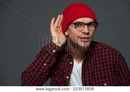 Intrigued young man in casual clothes put his hand to ear and overhears something on gray background