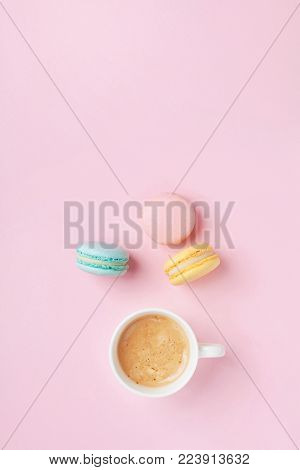 Morning cup of coffee and colorful cake macaron on pastel pink background top view. Cozy breakfast. Fashion flat lay. Sweet macaroons.