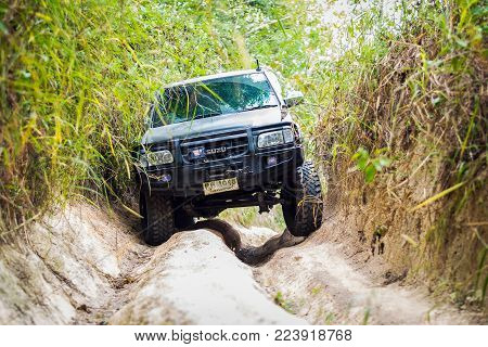 Chon Buri, Thailand-Dec 5, 2017: A 4 wheel drive is climbing on a difficult off-road in mountain forests in Thailand.