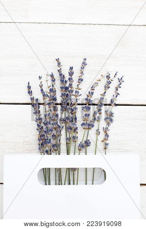 Bouquet of lavender in a paper white package on a wooden background. Vertical photo