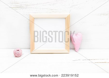 Square wooden frame and pink heart on a wooden background. Mock up
