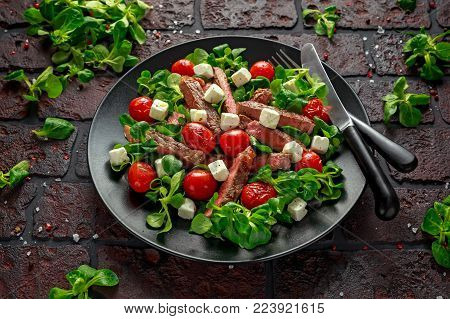 Juicy Beef Sirloin Steak Salad with roasted tomatoes, feta cheese and green vegetables in a black plate. healthy food.