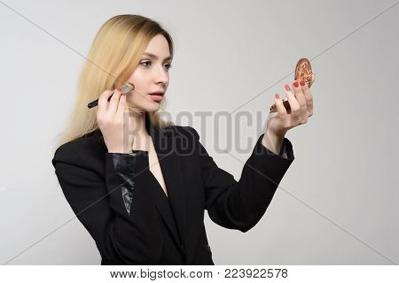 Beautiful Young Girl Putting On Lip Gloss In Front Of A Mirror