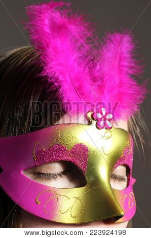 young woman with a pink an gold colored eye mask with feathers, eyes closed