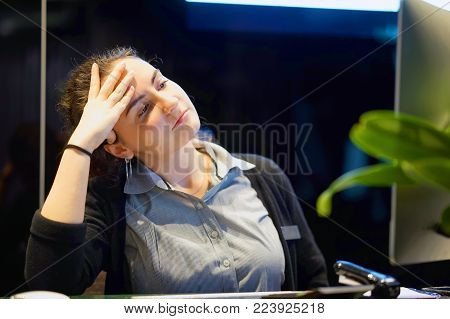 A woman-reception suffering from headache migraine pain. Health problem, stress and depression. Female holds head with hand. Hotel manager. Concept of health.