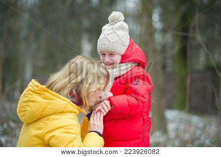 Young mother consoles the crying child. The girl has fallen during walk. For her it is sick and offensive. The loving mother calms the daughter. Against the background of the winter park.