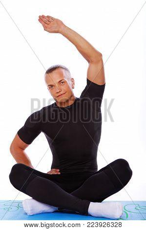 Portrait of sexy man doing exercises in studio