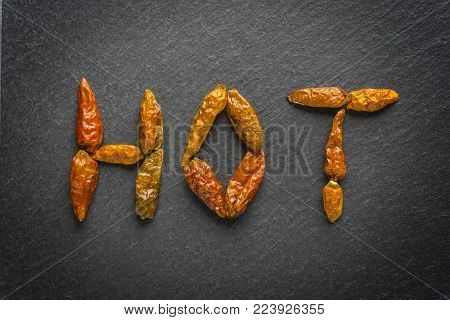 Red hot chilli peper on black background written hot