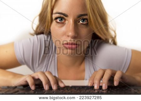 young attractive student girl or working woman sitting at computer desk in stress with tired blue eyes turned reddish after long hours working looking at screen in vision health care and internet addiction