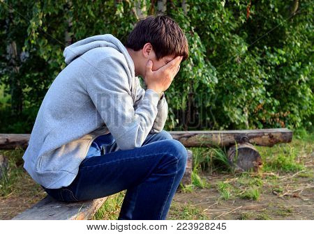 Stressed Young Man sit on the Bench outdoor