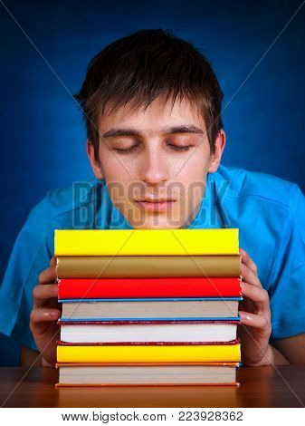 Tired Young Man with the Book on the Blue Background