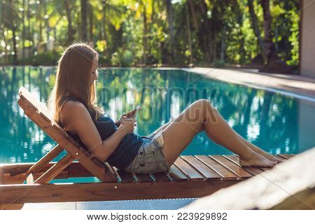 Happy Smartphone Woman Relaxing Near Swimming Pool. Beautiful Girl Using Her Mobile Phone App 4G Dat