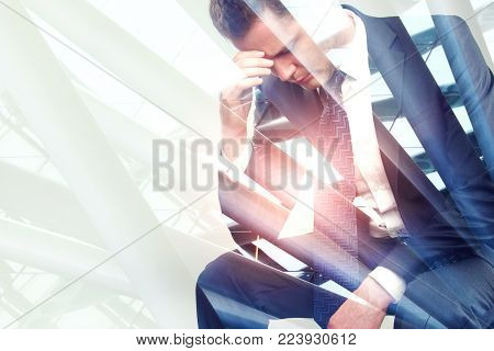 Thoughtful sad young businessman on abstract city background. Career and risk concept. Double exposure