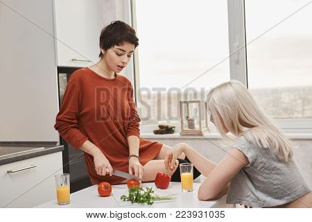 Indoor portrait of attractive hot woman sitting on table cutting tomotoe while her girlfriend drinks juice in kitchen. Lovely lgbt couple preparing healthy breakfast together. Couple concept