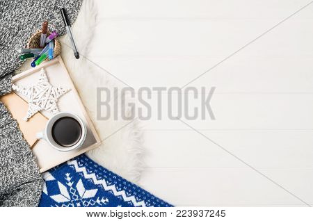 Mug with coffee and home decor on white, cosy wooden table background. Winter morning relax concept, top view. Frame with cup and copy space around objects.
