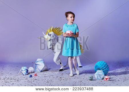 Pretty girl in an elegant blue dress for teenage girls with a make-up. Origami and minimalism. Fashion children. Designer collection. Charming teenager girl in studio holds an origami figure. Free space for text and advertising.