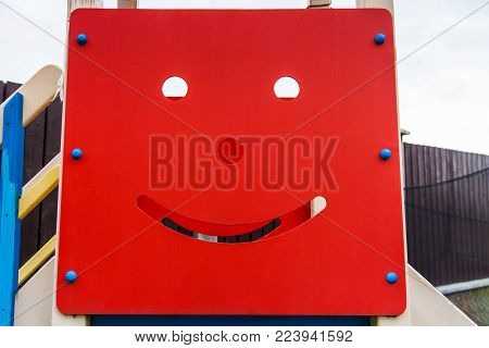 Smiling face carved on the surface of a wooden shield on the playground