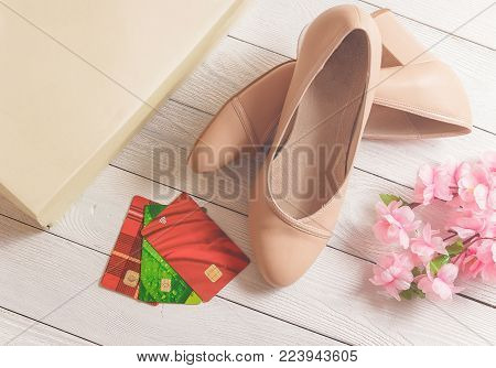 Box, credit cards and womans shoes lying on the white wooden background.