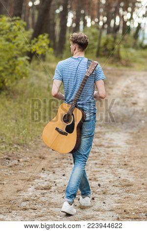 Talented guitarist playing forest hiking concept. Happiness of the artist. Unity with the nature.