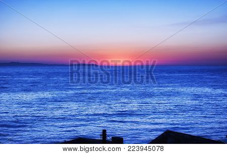 Laguna Beach California as the sun is setting over the Pacific Ocean.