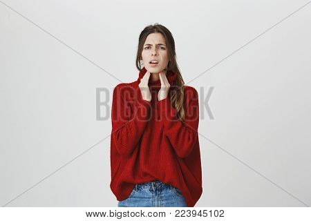 Waist-up portrait of sick ill dark-haired young female dressed in red sweater and jeans touches her neck, suffers from sore throat, feels bad, frowns her beautiful face. Negative face expression