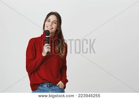 Microphone, music, songs, leisure time concept. Portrait of good-looking talented caucasian female singer looks at camera with broad smile, holds microphone in her hand, being happy. Positive pretty woman singing