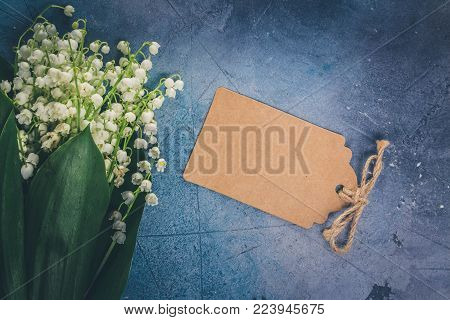 Lilly of the valley flowers on for Mothers Day on gray stone background with copy space on paper note, retro toned