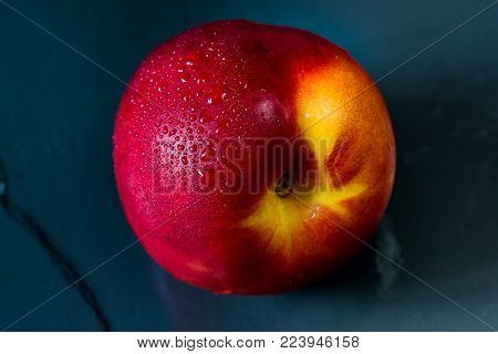 A ripe nectarine on a black  table