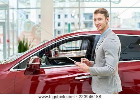 Portrait of handsome salesman smiling happily at camera standing by brand new luxury car in showroom and holding clipboard, copy space