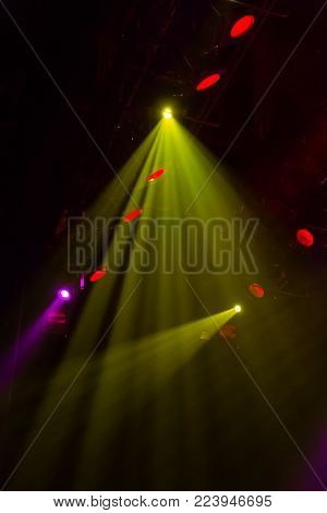 Lighting equipment on the stage of a theatre or concert hall. The rays of light from spotlights. Halogen and led light bulbs. Lens lighting.