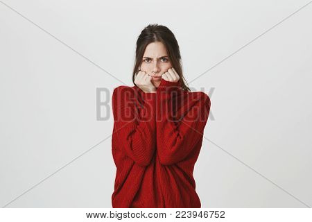 Waist-up portrait of annoyed angry young woman hiding her face, looks with furious and abused expression, frowns face in dissatisfaction, being displeased to hear bad words or comments about her appearance.