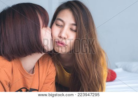 Beautiful young asian women LGBT lesbian happy couple sitting on bed hugging and smiling together in bedroom at home. LGBT lesbian couple together indoors concept. Spending nice time at home.