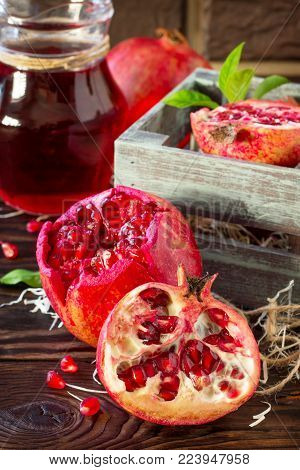 Freshly Squeezed Pomegranate Fruit Juice And Ripe Pomegranate On A Wooden Table. The Concept Of Nutr