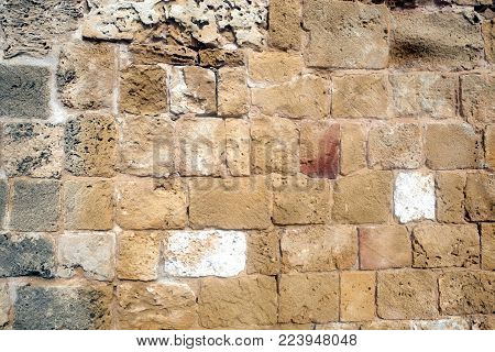 Antique wall from demaged sandy brown stones front view horizontal closeup