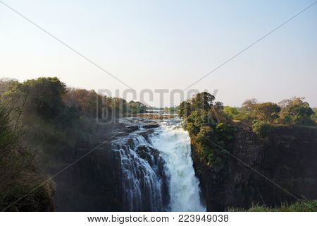 A view on a part of the Zambezi River and The Victoria Falls in Zimbabwe in summer. on the left the bush is hidden behind fog of the water. The water level is low