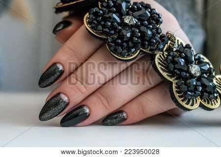 Beautiful winter manicure. Black lacquer with luster and white patterns of snow and frost. The white background is also with beautiful curled drawings.