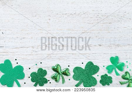 Saint Patricks Day border with green shamrock on white rustic board from above.