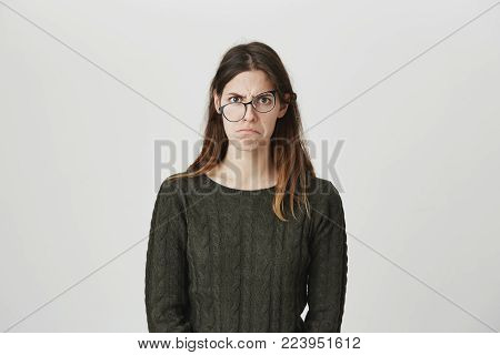 Indoor shot of upset female in spectacles being abused by someone, curves lips, looks unhappy at camera, wears green sweater, isolated against gray background with copy space for advertisement
