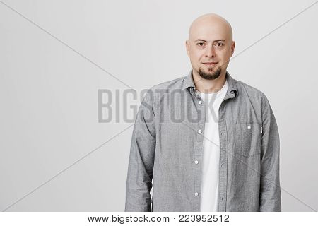 Horizontal portrait of Caucasian good-looking bald male model with beard dressed in gray shirt over white t-shirt, posing against gray studio wall, looking at camera with confident expression of face.