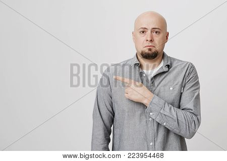 Dissatisfied upset male customer wearing long sleeved shirt frowning face looking sadly at camera, pointing fingers at copy space on studio wall. Caucasian bald man indicating something on studio wall