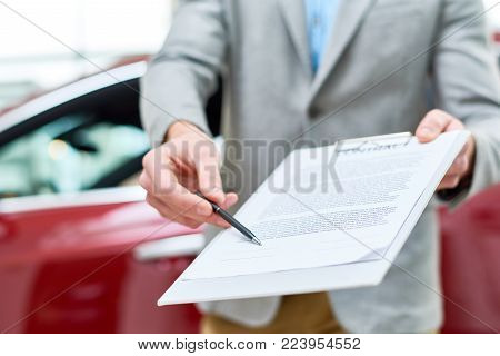 Close up view  portrait of unrecognizable car salesman handing purchase contract to client buying brand new car in luxury showroom