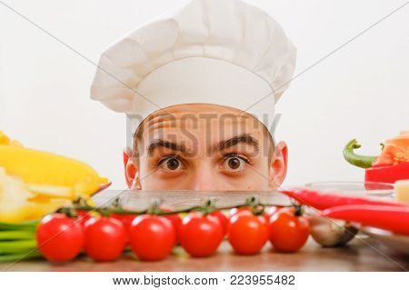 Man with cook cap on white background. Homemade food concept. Chef with vegetables on table. Cook with cheerful face in face close up.