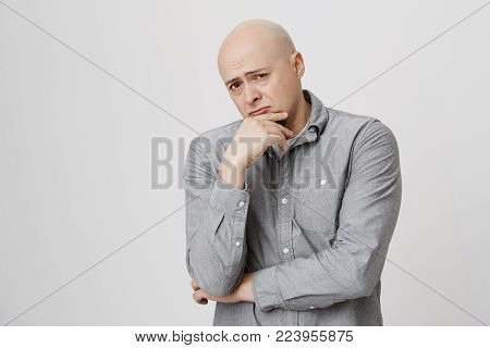 Bald businessman with beard keeps hand on chin, looks pensively at camera, frowns, isolated against gray background. Confident hairless european guy with thoughtful expression of face.