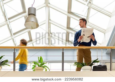 Portrait of young businessman wearing casual clothes reading newspaper standing at balcony in modern office building under glass roof