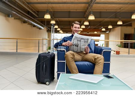 Portrait of handsome young man with suitcase reading newspaper sitting in armchair while waiting for check in in modem hotel