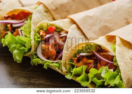 Stack of homemade whole wheat flour tortilla on wooden table background